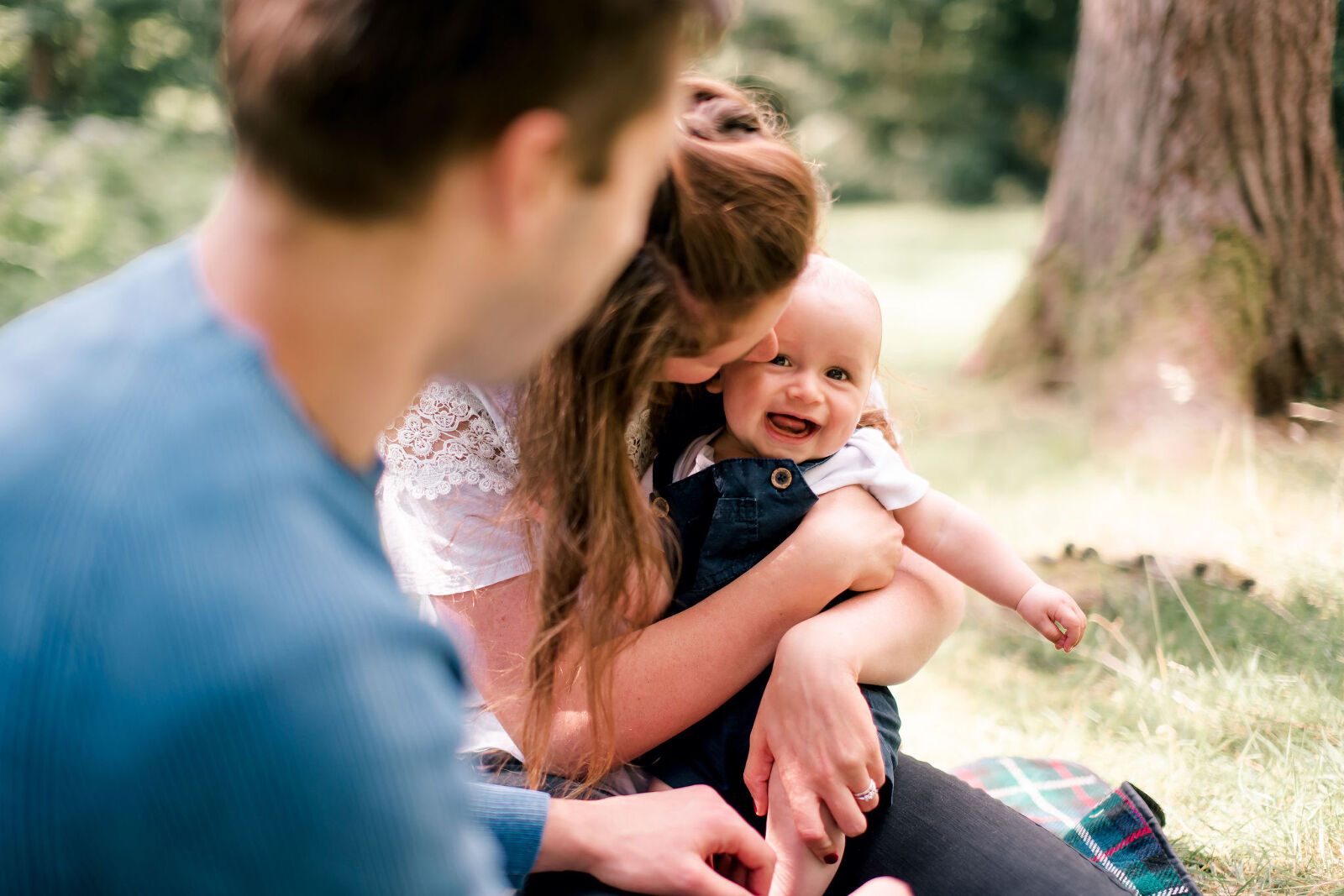 Mum and baby having a cuddle at a summer picnic